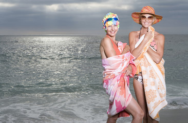 Mature woman in swimming cap by friend in sunhat on beach, smiling, portrait