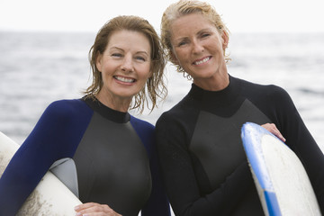 Female surfer and friend in wetsuits, smiling, portrait