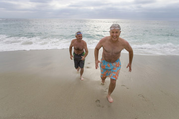Senior man and friend in swimming trunks running from sea, smiling, portrait