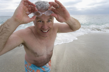Mature man in swimming trunks on beach adjusting goggles, smiling, portrait