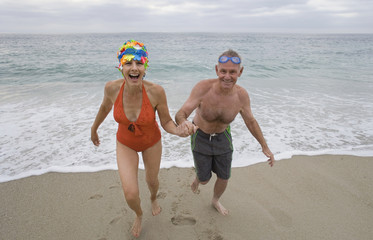 Mature couple in swimming costumes hand in hand running from sea, smiling, portrait