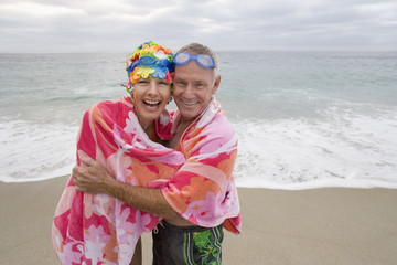 Mature couple wrapped in towel on beach, smiling, portrait