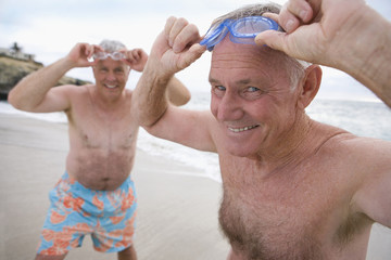 Mature man and friend in swimming trunks adjusting goggles on beach, smiling