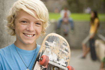 Boy (11-13) with skateboard by friends outdoors, portrait, close-up