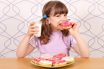 hungry little girl eating donuts and drink milk