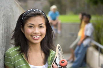 Teenage girl (13-15) with skateboard by friends outdoors, smiling, portrait