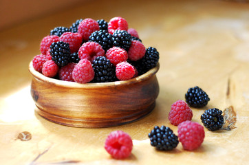 raspberries and blackberries in a wooden bowl