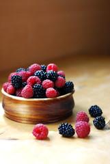 Raspberries and blackberries in a wooden bowl