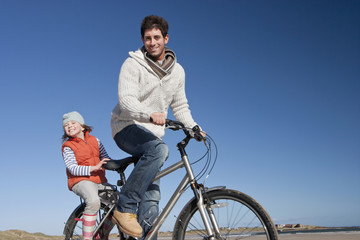 Portrait of father and daughter riding bicycle on sunny beach
