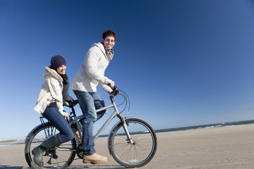 Smiling couple riding bicycle on sunny beach