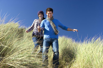 Couple descending grassy hill on sunny beach