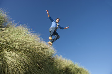 Man jumping above grass against sunny, blue sky