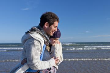 Happy couple hugging on sunny beach