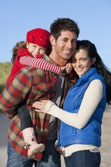 Portrait of smiling parents and daughter hugging on sunny beach