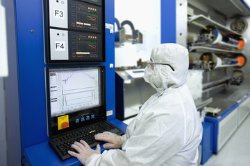 Engineer in clean suit working at computer in silicon wafer manufacturing laboratory