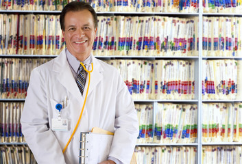 Portrait of smiling doctor in lab coat standing in front of filed medical records on shelf