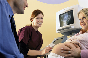 Nurse performing ultrasound examination on pregnant woman smiling at husband