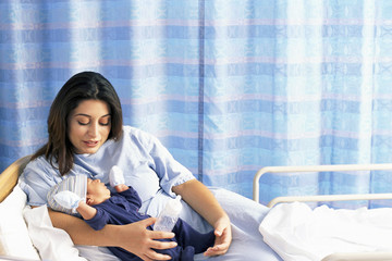 Mother holding baby son in hospital bed
