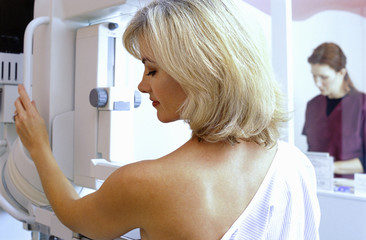Woman with bare chest undergoing mammogram with radiologist in background