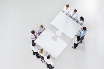 Two groups of business people connecting large jigsaw pieces