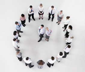 Portrait of businessman and businesswoman standing back to back in circle formed by co-workers