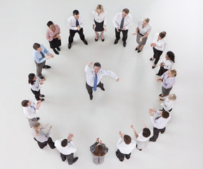 Portrait of businessman jumping in circle formed by clapping co-workers