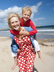 Portrait of smiling mother piggybacking daughter on sunny beach
