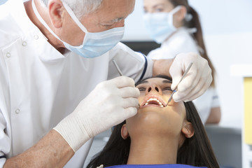 Close up of dentist examining patient's teeth with angled mirror and scrapper