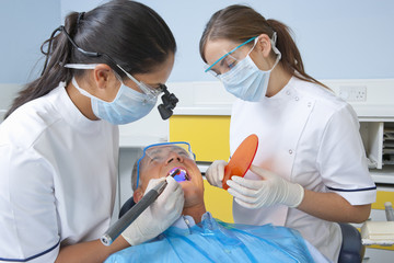 Dentist and dental assistant using ultraviolet light in patient's mouth