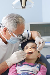 Dentist examining young patient's teeth with angled mirror and scraper