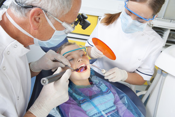 Dentist and dental assistant using ultraviolet light in young patient's mouth