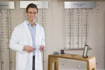 Portrait of smiling optometrist in front of eyeglasses rack