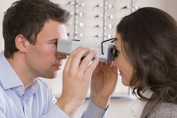 Close up of optometrist examining patient's eyes with eye test equipment