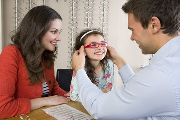 Mother watching optometrist help smiling daughter try on eyeglasses