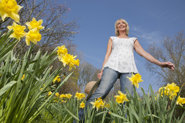 Smiling woman holding hat in sunny daffodil field