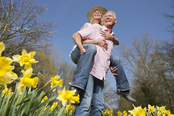 Happy senior couple piggybacking in sunny daffodil field