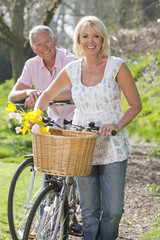 Portrait of smiling senior couple with spring flowers in bicycle basket