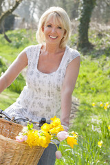 Portrait of smiling woman on bicycle with spring flowers in basket