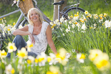 Portrait of smiling woman sitting in sunny daffodil field