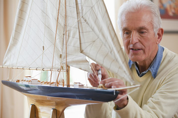 Senior man applying glue to model sailboat