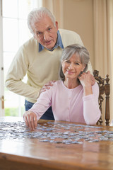 Portrait of smiling senior  couple assembling jigsaw puzzle on table