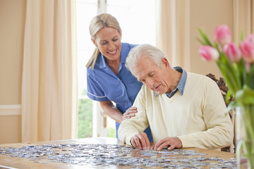 Smiling home caregiver watching senior man assemble jigsaw puzzle on table