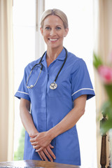 Portrait of smiling home caregiver wearing uniform and stethoscope