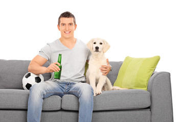 Man sitting at couch with his puppy and football
