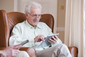 Senior man using digital tablet in armchair