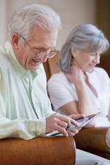 Senior man with eyeglasses using digital tablet