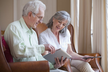 Smiling senior couple using digital tablets in armchairs