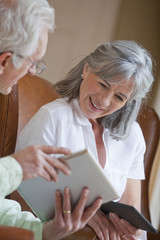 Smiling senior couple using digital tablets