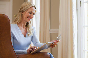 Smiling woman using digital tablet in armchair