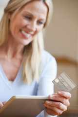 Close up of woman holding credit card and digital tablet